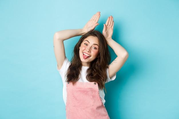 Portret pięknej dziewczyny glamour obchodzi wielkanoc, pokazując uszy królika z rękami nad głową, uśmiechając się radosny, stojąc na niebieskim tle.