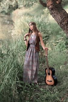 Portret pięknej dziewczyny hippie z gitarą stojącą w pobliżu stawu