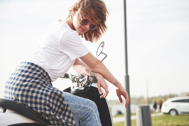 Portret pięknej dziewczyny hipster siedzi na czarnym skuterze retro, uśmiechając się, pozując i ciesząc się ciepłym wiosennym słońcem.