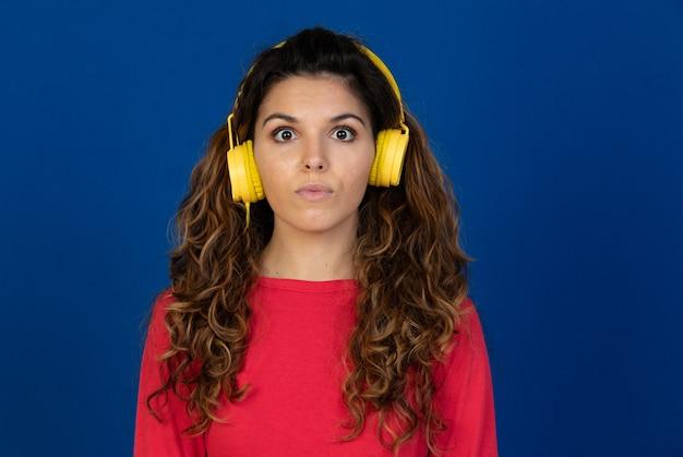 Portret pięknej dziewczyny kaukaski z kręconymi włosami i słuchawki słuchania muzyki na białym tle na białej ścianie