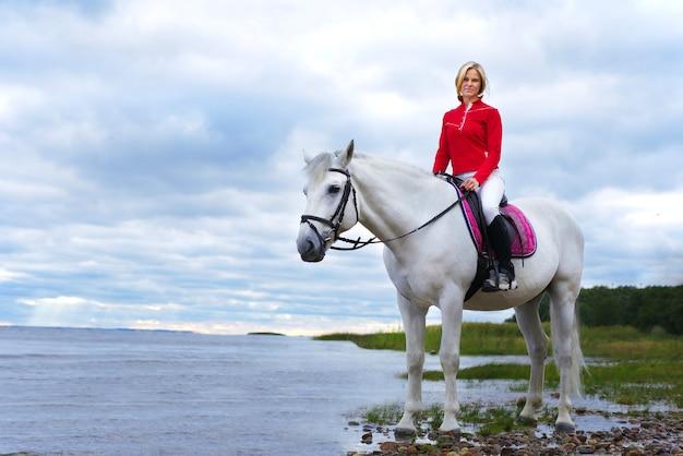 Portret pięknej dziewczyny, młoda kobieta, jeździec jeździecki na białym koniu w koszulce polo, jazda konna