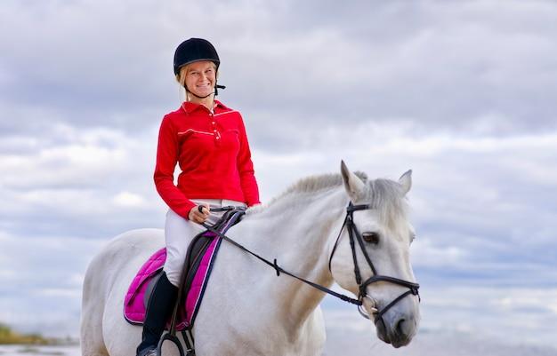 Portret pięknej dziewczyny młoda kobieta jeździec na białym koniu w kasku i koszulce polo