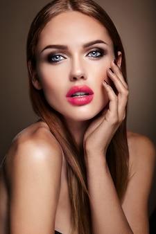 Portret pięknej dziewczyny model z wieczorowy makijaż i romantyczną fryzurę. czerwone usta