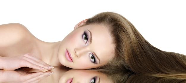 Portret pięknej dziewczyny nastolatki z długimi prostymi włosami, na białym tle