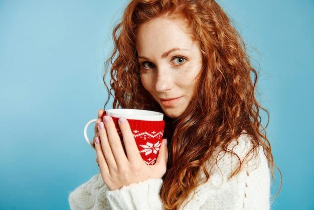 Portret pięknej dziewczyny picia gorącej herbaty lub kawy