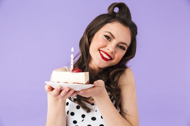 Portret pięknej dziewczyny pin-up w jasnym makijażu stojącej na białym tle nad fioletową ścianą, trzymającej talerz z kawałkiem ciasta
