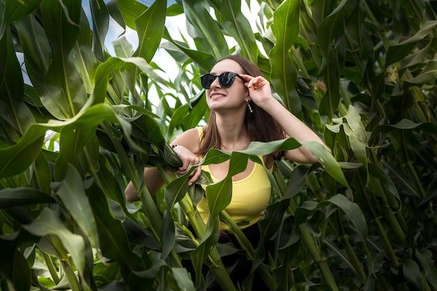 Portret pięknej dziewczyny pozuje w zielonym polu kukurydzy, ciesz się letnim wolnym czasem