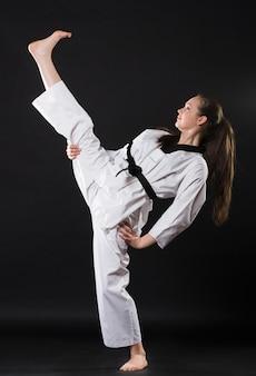 Portret pięknej dziewczyny sztuk walki w kimonie ćwiczących karate kata na ciemnym tle
