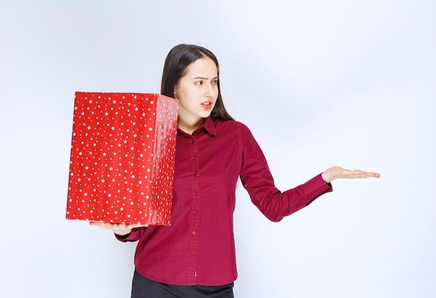 Portret pięknej dziewczyny trzymającej pudełko i odwracając się nad białą ścianą.