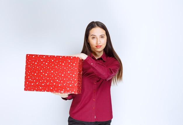 Portret pięknej dziewczyny trzymającej pudełko nad białą ścianą.