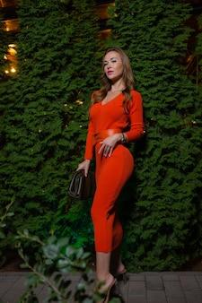 Portret pięknej dziewczyny w bordowej czerwonej sukience na tle liści winogron w parku