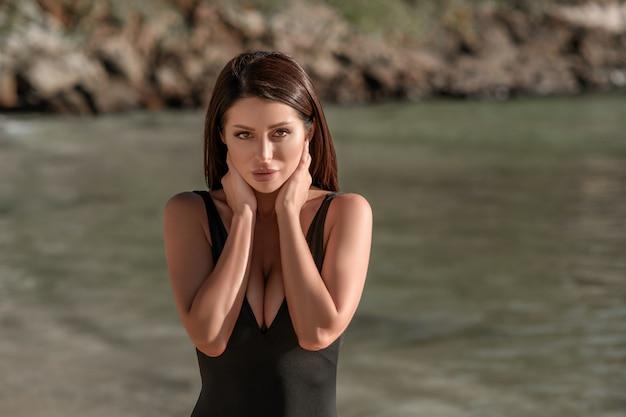 Portret pięknej dziewczyny w czarnym stroju kąpielowym, który dotyka jej szyi na plaży. seksowna sesja zdjęciowa