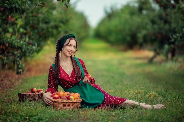 Portret pięknej dziewczyny w czerwonej rustykalnej sukni z warkoczami