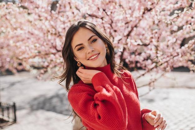 Portret pięknej dziewczyny w czerwonym swetrze w pobliżu sakury. urocza kobieta w stroju cashemere, uśmiechając się i patrząc w kamerę w ogrodzie