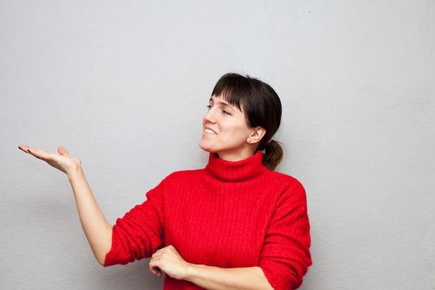 Portret pięknej dziewczyny w czerwonym swetrze, wskazując na bok