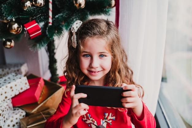 Portret pięknej dziewczyny w domu przy choince