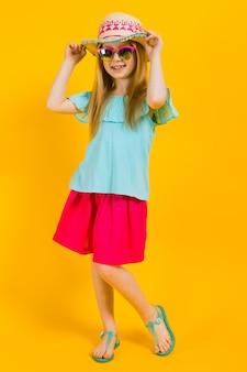 Portret pięknej dziewczyny w kapeluszu, okularach przeciwsłonecznych, letniej sukience i sandałach.