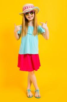 Portret pięknej dziewczyny w kapeluszu, okulary przeciwsłoneczne, letnia sukienka i sandały.