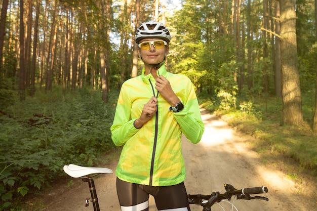 Portret pięknej dziewczyny w kasku i okularach, która po przejażdżce rowerem rozpina jaskrawozieloną wiatrówkę