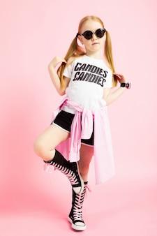 Portret pięknej dziewczyny w krótkich spodenkach, koszulce i wysokich tenisówkach.