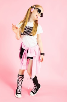 Portret pięknej dziewczyny w krótkich spodenkach, t-shirt i wysokie trampki.