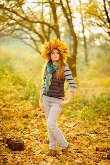 Portret pięknej dziewczyny w niebieskiej kamizelce stoi na tle bajecznej jesieni. na głowie jest bujny wieniec z jesiennych liści. bardzo delikatny model patrząc w kamerę.