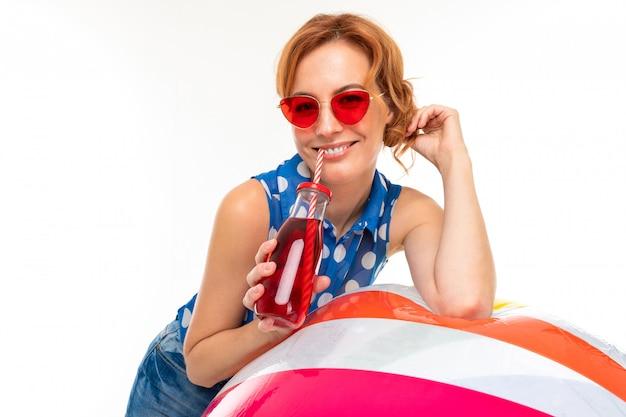 Portret pięknej dziewczyny w okularach przeciwsłonecznych trzyma nadmuchiwaną dużą piłkę do pływania i szklany kubek ze słomką na białej ścianie