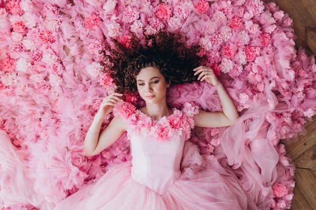 Portret pięknej dziewczyny w różowej sukience. młoda kobieta z kędzierzawym włosy kłama na różowym, kwiecistym tle, odgórny widok. emocjonalny tragarz kobiety.