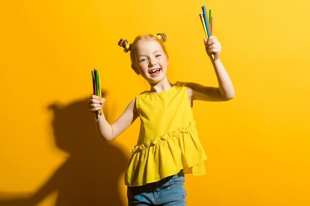 Portret pięknej dziewczyny w żółtej bluzce i niebieskich dżinsach.