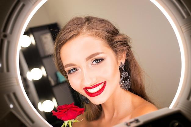 Portret pięknej dziewczyny z czerwonymi ustami i różą