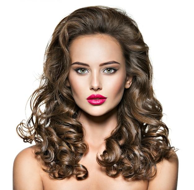 Portret pięknej dziewczyny z długimi brązowymi włosami kręconymi. piękna twarz og młoda dorosła dziewczyna z czerwoną szminką