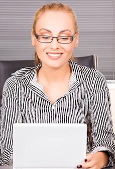 Portret pięknej dziewczyny z komputerem w biurze