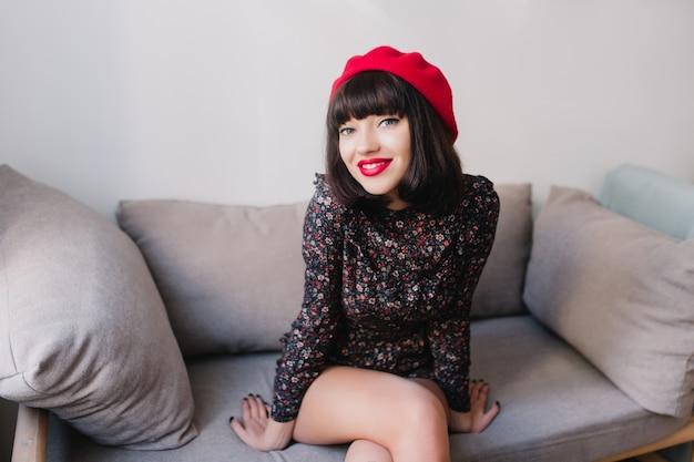 Portret pięknej dziewczyny z krótkimi ciemnymi włosami, siedzącej na szarej kanapie i uwodzicielsko uśmiechnięta. atrakcyjna młoda kobieta śmiejąca się z modną fryzurę na sobie francuski strój chętnie pozuje w jasnym pokoju