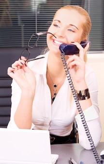 Portret pięknej dziewczyny z telefonem i notatnikiem w biurze