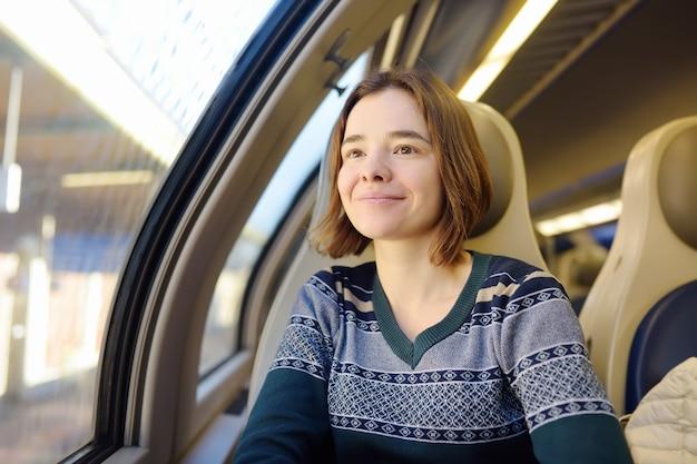 Portret pięknej dziewczyny zamyślony marzy w wagonie pociągu.