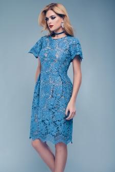 Portret pięknej eleganckiej kobiety w modnej niebieskiej sukience