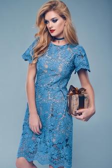 Portret pięknej eleganckiej kobiety w modnej sukni z prezentem