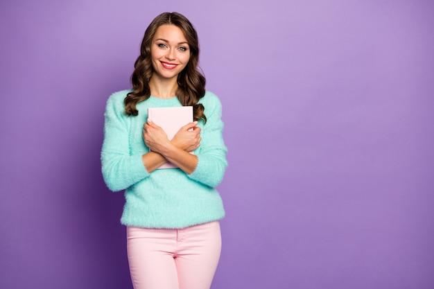 Portret pięknej falistej damy trzymaj ulubioną powieść miłosną blisko piersi zakończoną czytaniem poczuj romantyczne emocje noś rozmyty sweter w pastelowych różowych spodniach.