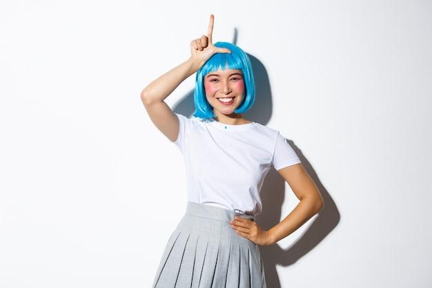 Portret pięknej głupiej azjatyckiej dziewczyny świętuje halloween, pokazując przegrany gest na czole i uśmiechając się