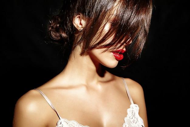 Portret pięknej gorącej ślicznej seksownej brunetki kobiety z czerwonymi wargami na czarnym tle