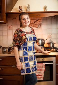 Portret pięknej gospodyni domowej pozuje przed kuchenką gazową z rondlami