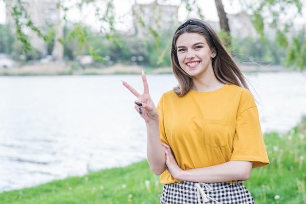 Portret pięknej i młodej dziewczyny rasy kaukaskiej pokazującej znak pokoju