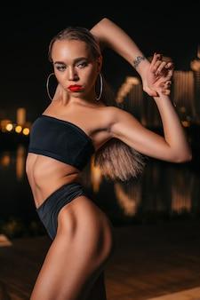 Portret pięknej i seksownej dziewczyny w czarnym stroju kąpielowym na nocnym mieście