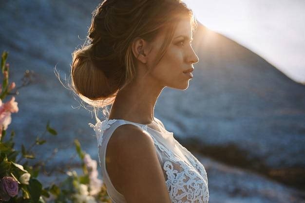 Portret pięknej i zmysłowej blondynki modelki z modelowania stylową fryzurę w modnej białej koronki sukni pozowanie na zachód słońca