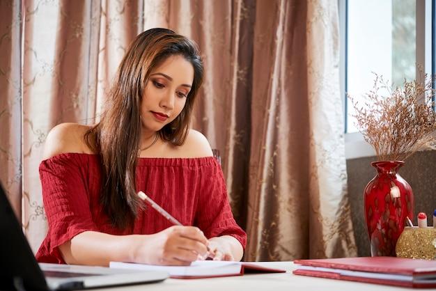Portret pięknej indyjskiej młodej kobiety piszącej myśli i pomysły w terminarzu lub dzienniku, gdy siedzi przy stole w domu