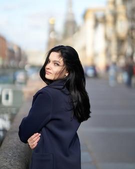 Portret pięknej, inteligentnej brunetki, która idzie ulicą sankt petersburga