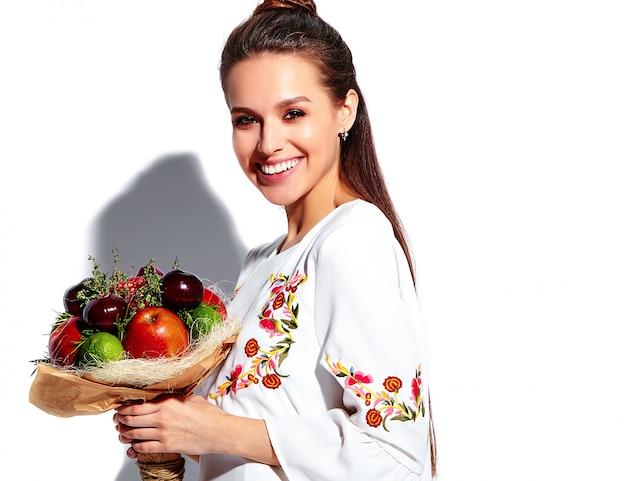 Portret pięknej kaukaski uśmiechnięta brunetka modelka w białej letniej stylowej sukni z niezwykłym kreatywnym bukietem kwiatów
