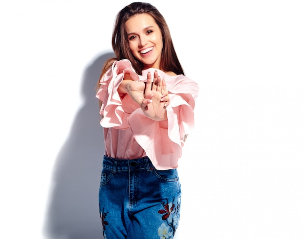 Portret pięknej kaukaski uśmiechnięta brunetka modelka w jasnej różowej bluzce i letnich stylowych niebieskich dżinsach z nadrukiem kwiatów