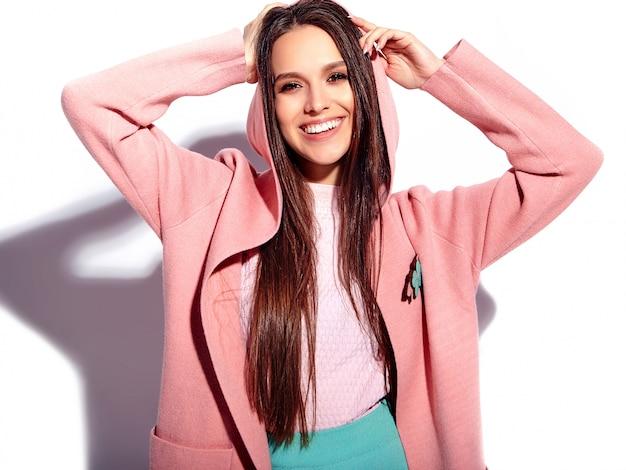 Portret pięknej kaukaski uśmiechnięta brunetka modelka w jasny różowy płaszcz i letnią stylową niebieską spódnicę