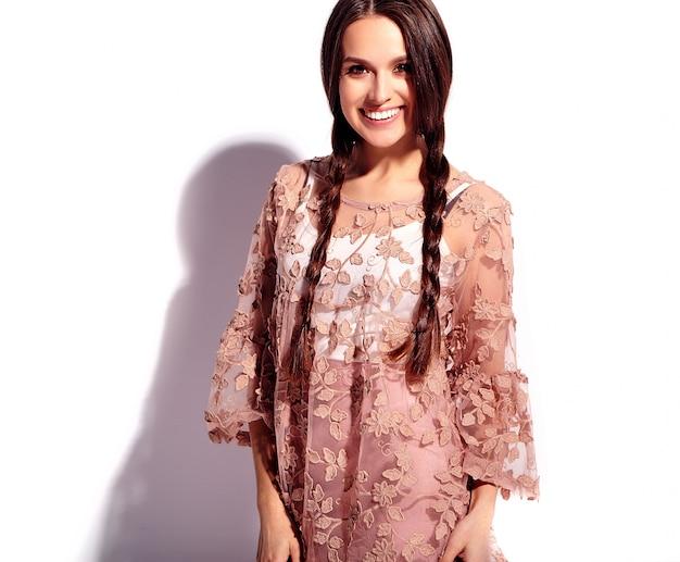 Portret pięknej kaukaski uśmiechnięta brunetka modelka z podwójnymi warkoczami w jasne różowe lato stylowe ubrania